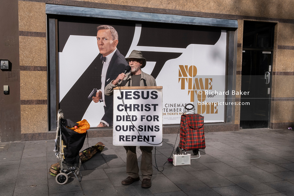 A Christian man who frequents the West End carrying religious messages from the Bible, stands in front of a poster for Daniel Craig's last appearance as James Bond in the film 'Not a Day to Die', which has finally opened around the country, delayed after the Covid pandemic, on 12th October 2021, in London, England.