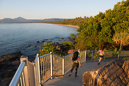 Two female joggers run down a path at sunrise above Four Mile Beach in Port Douglas, Queensland, Australia.