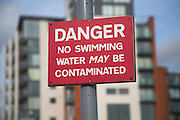 Red sign warning of Danger of swimming in water that may be contaminated, Ipswich Wet Dock, Suffolk, England