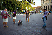 Four dog walkers stop and talk as their dogs leads become entwined in the Piazza Bra in Verona, Italy