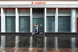 Glasgow, Scotland, UK. 12 March 2021. On the day Covid-19 lockdown is relaxed slightly in Scotland the city centre streets in Glasgow city centre remain almost deserted virtually all shops ad cafes are still closed. Pic;  Branch of Vodafone is closed and shuttered. Iain Masterton/Alamy Live News
