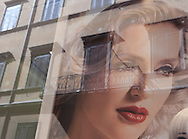 Traditional architecture reflected on fashion store windows at Via del Como in Rome, Italy.