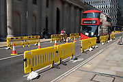 In the City of London, yellow barriers are placed to mark out new road layouts for social distancing on the day that it was announced that the Coronavirus lockdown measures are set to ease even further and the quiet city starts coming to an end, on 23rd June 2020 in London, England, United Kingdom. As of today the government has relaxed its lockdown rules, and is allowing some non-essential shops to open with individual shops setting up social distancing queueing systems.