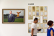 Employees walk past a portrait of billionaire Li Jinyuan, chairman of Tiens Group, displayed on a wall next to award certificates at the companys headquarters in Tianjin, China on Tuesday, Aug. 9, 2016. Tiens is a direct sales firm specializing in health and beauty products.