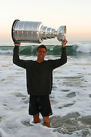 24 August 2002: Detroit Red Wings professional hockey player Chris Chelios stands in the surf for a candid portrait while he  carries the NHL Stanley Cup away over his head in front of his Malibu summer home in Los Angeles. EXCLUSIVE. .<br />