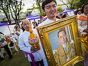 "24 JULY 2014 - BANGKOK, THAILAND:  Thai civil servants, holding a portrait of Bhumibol Adulyadej, the King of Thailand, prepare to march in parade honoring the King. The Thai Junta is organizing a series of public events throughout Thailand meant to bolster public opinion. The events are called ""restoring happiness to the people"" parties. They feature historic pageants, music, food, health checks and free haircuts. The party in Bangkok is on Sanam Luang, the Royal Parade Ground, which is near the Grand Palace and the Ministry of Defense.   PHOTO BY JACK KURTZ"
