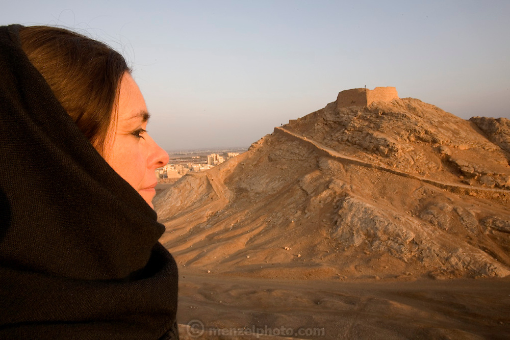 Faith Daluisio's profile and an abandoned Zoroastrian tower of silence. Yazd, Iran.  Zoroastrians brought their dead to towers of silence to be eaten by birds before the practice was outlawed by the Iranian government.  The bodies of the dead were considered unclean by Zoroastrians and so corpses were put atop the towers (often hilltops) so that the earth would not be polluted by the remains. Today Zoroastrians in the community are buried in a nearby cemetary, although placed so that the body does not touch the earth. MODEL RELEASED.