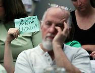 """A person holds up a small sign reading """"health reform now"""" at a town hall meeting on healthcare reform hosted by Rep. Mike Coffman (R-CO) in Littleton, Colorado August 12, 2009. REUTERS/Rick Wilking (UNITED STATES POLITICS HEALTH)"""