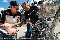 Harley-Davidson motorcycle designer Paul Martin judges Christian Rivard's bike in the Ride-In Show at the Harley-Davidson display Wednesday during Daytona Bike Week. FL, USA. March 12, 2014.  Photography ©2014 Michael Lichter.