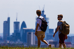 Two men walk across the London skyline on Parliament Hill on another hot day in London. London, July 03 2018.