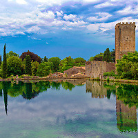 Medieval Tower and lake. Garden of Ninfa. Lazio. Italy. The beautiful and romantic Garden of Ninfa is located in the territory of Cisterna di Latina within the central Italian region of Lazio, Italy.