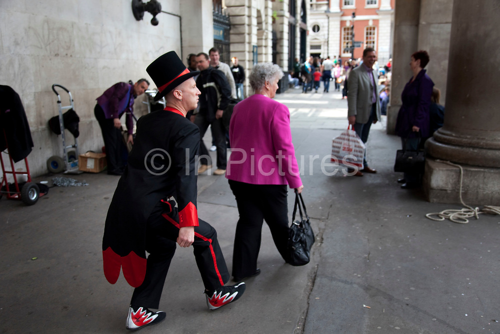 Covent Garden in the West End of London. Street performer mimicks a lady walking past.