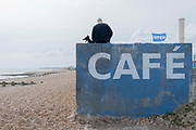 A pet owner and his dog at the outdoor seafront cafe that was once a part of the St Leonards Bathing pool opened 1933, on 3rd May 2021, in St Leonards, Sussex, England.