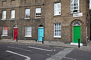 Colourful front doors on a classic Georgian terraced street of houses in Waterloo in London, United Kingdom. Theed Street is just off Roupell Street and consists of nineteenth-century workers cottages, and was first developed in the 1820s. This is on one of the capitals better-preserved streets after many were destroyed during the Blitz in WW2. This is a preservation area whose are from the Georgian period in a backstreet.