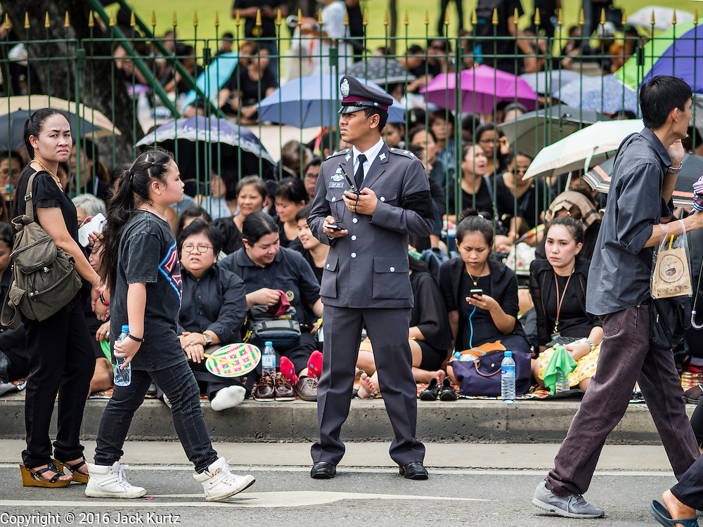 14 OCTOBER 2016 - BANGKOK, THAILAND:  A Thai police officer watches mourners on Rajadamnoen Avenue before the King's body was brought to the Grand Palace. King Bhumibol Adulyadej died Oct. 13, 2016. He was 88. His death comes after a period of failing health. With the king's death, the world's longest-reigning monarch is Queen Elizabeth II, who ascended to the British throne in 1952. Bhumibol Adulyadej, was born in Cambridge, MA, on 5 December 1927. He was the ninth monarch of Thailand from the Chakri Dynasty and is known as Rama IX. He became King on June 9, 1946 and served as King of Thailand for 70 years, 126 days. He was, at the time of his death, the world's longest-serving head of state and the longest-reigning monarch in Thai history.    PHOTO BY JACK KURTZ