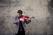 A street musician playing a violin on the end of Charles Bridge in Prague.