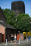 View of Grenfell Tower behind green tress June 16th 2017, London, United Kingdom. A couple walks past. Grenfell Tower burned out after a catastophic fire killing more than 58 people. The tower caught fire early Wednesday morning and final casualty figueres may end up to be many more with police not expecting to be able to find and recover all bodies and to find all missing people. No fire sprinkler in place and cheap cladding made with plastic is so far blamed for the ferocious fire.