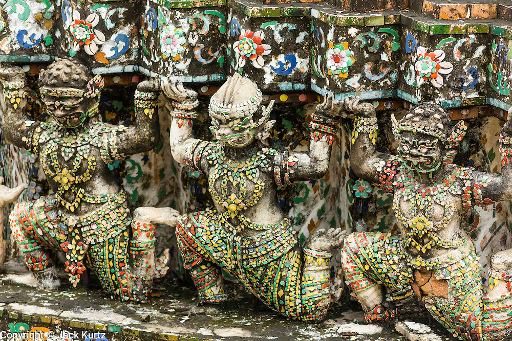 """23 SEPTEMBER 2013 - BANGKOK, THAILAND: Figures of Hanuman, the Monkey God at Wat Arun. The figures are scheduled to be a part of the renovation of the temple. The full name of the temple is Wat Arunratchawararam Ratchaworamahavihara. The outstanding feature of Wat Arun is its central prang (Khmer-style tower). The world-famous stupa, known locally as Phra Prang Wat Arun, will be closed for three years to undergo repairs and renovation along with other structures in the temple compound. This will be the biggest repair and renovation work on the stupa in the last 14 years. In the past, even while large-scale work was being done, the stupa used to remain open to tourists. It may be named """"Temple of the Dawn"""" because the first light of morning reflects off the surface of the temple with a pearly iridescence. The height is reported by different sources as between 66,80 meters and 86 meters. The corners are marked by 4 smaller satellite prangs. The temple was built in the days of Thailand's ancient capital of Ayutthaya and originally known as Wat Makok (The Olive Temple). King Rama IV gave the temple the present name Wat Arunratchawararam. Wat Arun officially ordained its first westerner, an American, in 2005. The central prang symbolizes Mount Meru of the Indian cosmology. The temple's distinctive silhouette is the logo of the Tourism Authority of Thailand.           PHOTO BY JACK KURTZ"""