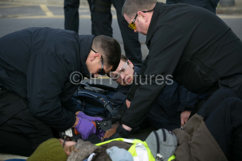 Climate activists block a road by Heathrow in protest against the proposed third runway November 19th 2016 in Heathrow, London,United Kingdom. Police cutting free the activists. Police were out in force and after 30 minutes the the roads were clear. 9 Arrests were made at this point of the protests which was part of larger act of civil disobedience.