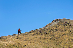 Mountain biker walking bike on uphill in alpine landscape, Tyrol, Austria