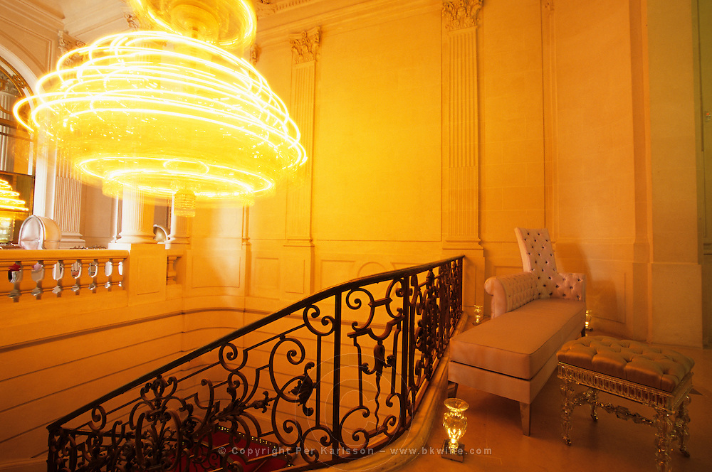 The main stairway and entrance with the 800 kilogram revolving crystal chandelier, wrought iron railing, satin and crystal chaise-longue canapé, crystal piedestal, and floor light. At The Baccarat museum, shop, restaurant at the Hotel de Noailles in Paris. Designed by Philippe Starck. The Baccarat museum: the main stairway with its 800kg revolving crystal chandelier and a crystal chaise-longue