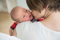 Mother kissing newborn baby boy while holding in her arms, Munich, Bavaria, Germany