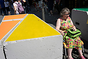 Woman in a beautiful and brightly coloured dress and passes painted colourful anti-vehicle security barriers made of concrete as part of the now familiar anti terror attack security in Leicester Square in London, England, United Kingdom.