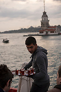 A waiter serves tea at an outdoor cafe in Üsküdar, a district in Istanbul, Turkey.  The landmark lighthouse called the Maiden's Tower is in the background.