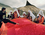 "The bride, along with her sisters and other close female relatives are squatting under a red cloth in front of the ceremonial yurt while the men around the cloth are throwing candies on the cloth and distributing ""bortsok"" (fried dough), to bring good luck to the wedding. Meanwhile, the girls are weeping and crying, signifying the upcoming ""loss"" of the bride to her husdand's family.<br /> <br /> The Kyrgyz wedding ceremony of Koormoochoo Saïra (son of Yunus Amid) in Utch Djelgha summer camp, 5th August 20005.<br /> <br /> Adventure through the Afghan Pamir mountains, among the Afghan Kyrgyz and into Pakistan's Karakoram mountains. July/August 2005. Afghanistan / Pakistan."