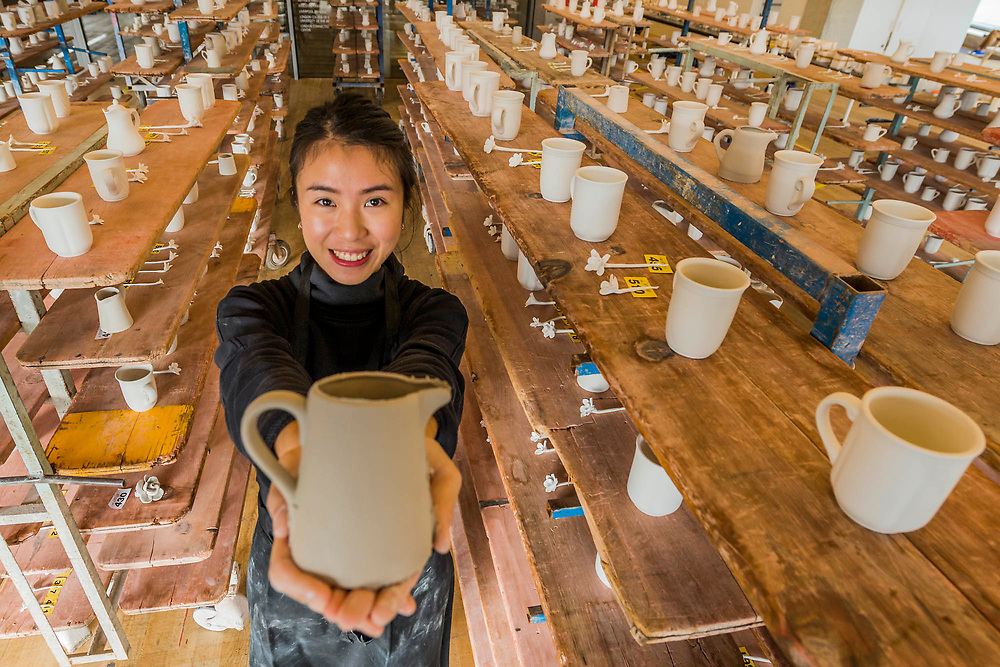 Student Bridgette Chang with racks of completed ceramics - FACTORY: the seen and the unseen - an installation, in the form of a ceramics factory, by artist Clare Twomey. It is set up in the Blavatnik Building of the Tate Modern and launches the second year of Tate Exchange which, over 2017 and 2018, will focus on the theme of production.