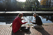 A couple of friends share a bottle of sanitizer by the Regents Canal in Hackney during the second coronavirus national lockdownon on 7th of November 2020, East London, United Kingdom. The canal is home to many living in boats and the canal has become both a home to many and a place to spend time on a sunny day. <br /> The lockdown restrictions mean that people are only allowed to meet outside, in pairs and only if keeping social distance.
