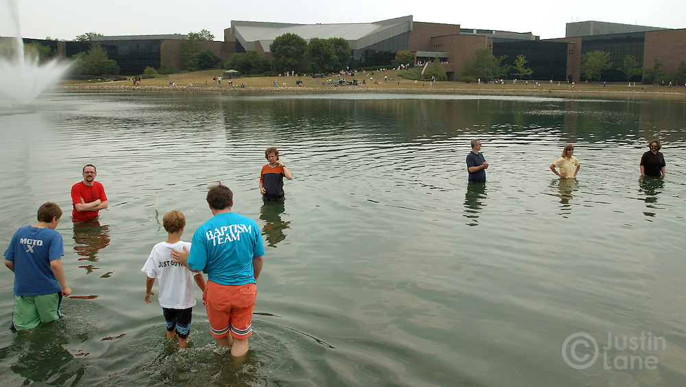 A young boy, left,  is led into the water for his baptism at Willow Creek Community Church, seen in background, in South Barrington, IL on June 26, 2005. The church holds regular mass baptisms at which hundreds of people are baptized in the church's small lake.