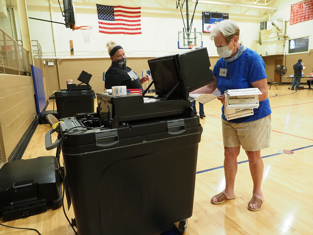 Suzanne Mutchie feeds each received absentee ballot into the optical scanner so it can be counted. Each ballot is meticulously tracked for verification purposes.
