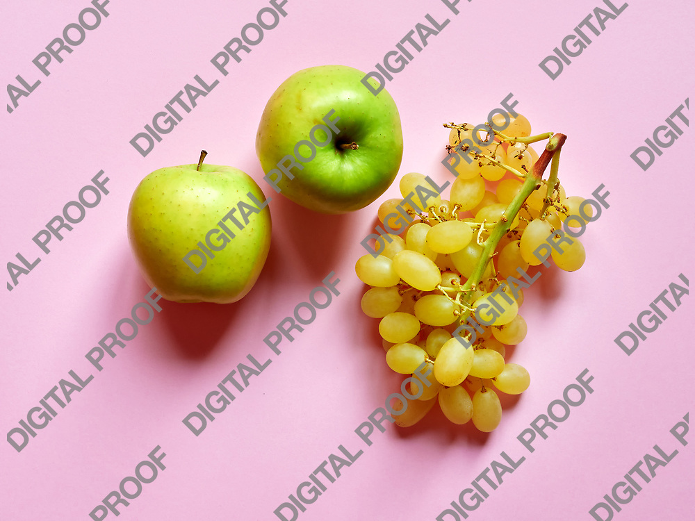 Above view of isolated set of a green apples with a bunch of sweet seedless grapes in studio with millennial pink background