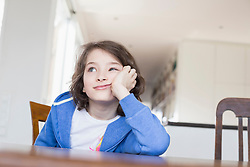 Girl sitting at wooden table, looking away