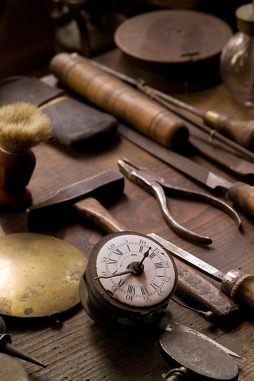 Close-up view of a vintage, 19th Century watchmaker's tools on a wooden work bench, Musee Regionale de Val de Travers, Motier, Switzerland museum. The precision tools include a hammer, 2 awl's, a glass jar with brown cap, pliars, brown wooden pedestal, sharpening stones, and brush, brass pendulum to a grandfather clock and a timepiece.