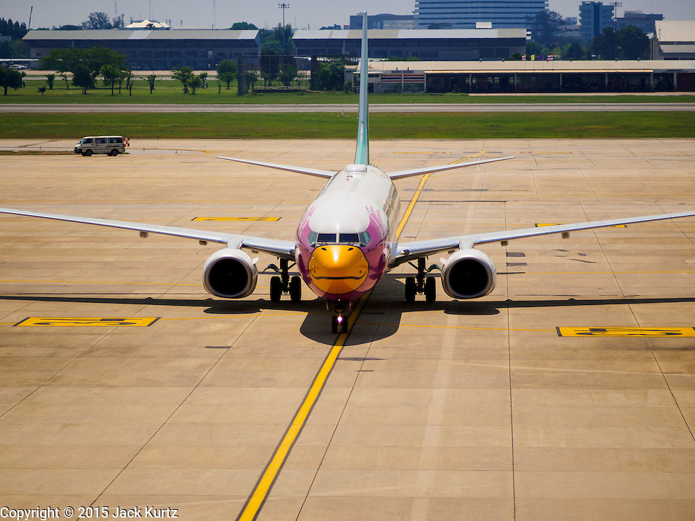 02 APRIL 2015 - BANGKOK, THAILAND:  A NOK Airlines Boeing 737 taxis to a gate at Don Mueang Airport in Bangkok. The International Civil Aviation Organization (ICAO), a United Nations agency, issued a report critical of record keeping and maintenance reports for Thailand's civil aviation industry, including most Thai air carriers. The ICAO report allegedly showed that the Thai Department of Civial Aviation (DCA) was able to meet only 21 out of 100 ICAO requisites. Several Asian countries, including South Korea, Japan and China have imposed limits of Thai registered aircraft since the release of the ICAO report and the European Union has begun to review the safety records of Thai Airways International (THAI) aircraft that fly to Europe.    PHOTO BY JACK KURTZ