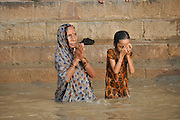 Mother and daughter bathe in the Ganges River. Varanasi, Uttar Pradesh, India