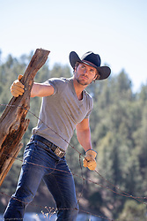 rugged good looking cowboy by a rustic fence on a ranch