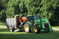 Tractor driven machinery sweeping and vacuuming the lawns of Windsor Great Park, UK