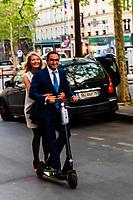 An elegant Parisian couple ride down Avenue Marceau on an electric scooter, Paris, France.