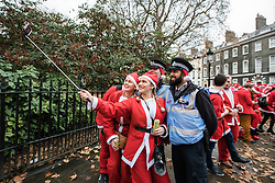 © Licensed to London News Pictures. 10/12/2016. London, UK. Santas take a selfie with two policemen as  thousands descend on central London for the annual Santacon Parade. Photo credit: Rob Pinney/LNP