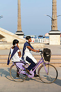 Two schoolgirls - one riding side-saddle or pillion - cycle to school along the Promenade, Pondicherry, India. Pondicherry now Puducherry is a Union Territory of India and was a French territory until 1954 legally on 16 August 1962. The French Quarter of the town retains a strong French influence in terms of architecture and culture.