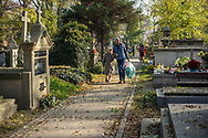 Elderly lady and man walking with plastic bags filled with flowers over Rakowicki cemetery in Krakow, Poland 2019.