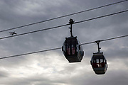 Two Emirates Air Line Cable Car ravel across the River Thames between Greenwich Peninsula and the Royal Docks in London, England, United Kingdom.  An Aeroplane passes by in the sky full of moody clouds.  The Air Line opened in 2012  and was built by Doppelmayr with sponsorship from the airline Emirates.