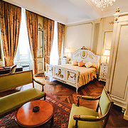 A lavish hotel room in a luxury hotel in Beaune, Burgundy, France, with a Queen bed, sitting area, and chandelier.