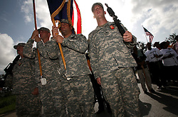 29 August 2006. New Orleans, Louisiana. Lower 9th ward. Great Flood commemoration and memorial ceremony; to 'honor and remember our loved ones who have passed. <br /> Members of the Louisiana National Guard who helped rescue people from the floods of a year ago return to the devastated neighbourhood  to form an honor guard as people prepare to pay tribute to and salute the victims of hurricane Katrina, which struck one year ago today.<br /> Photo Credit©; Charlie Varley/varleypix.com
