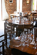 In the tasting room: tables set up for a big wine tasting with glasses on the tables, lit by sunshine coming through the windows. Bodega Juanico Familia Deicas Winery, Juanico, Canelones, Uruguay, South America