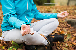 Low section of woman meditating while sitting on a rock in autumn scenery