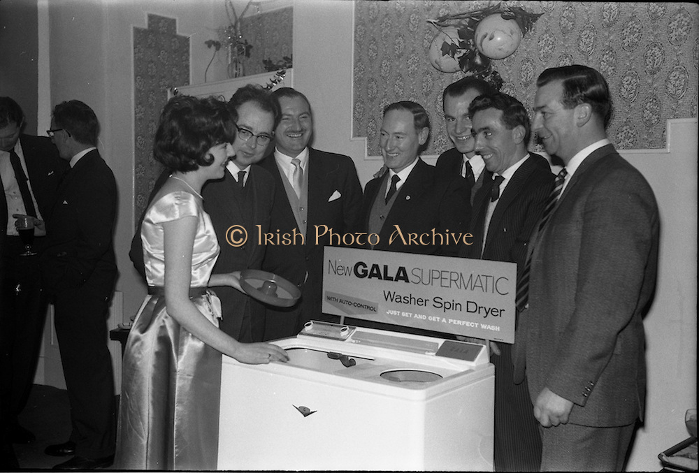 17/12/1962<br /> 12/17/1962<br /> 17 December 1962<br /> A.E.I. Gala reception at Shangri-la Hotel, Dalkey, Dublin, where a Gala Supermatic washing machine was presented to the Variety Club of Ireland for their Easter Draw by Gala. Picture shows AEI Gala demonstrator Miss Patricia Kavanagh chatting with Gala dealers (l-r), Mr. Sean Cooney, M.S.G., ESB Portlaoighise; Mr. D.G. P. Hanley, Gala Representative for South of Ireland; Mr. R.J. Kilbride, Manager, Electrical Department, Walkers Ltd.; Mr. Sean Hayes, Gala Representative for Northern Area; Mr. Victor Mancais, Salesman, Dockrells and Mr. J.G. Byrne, Manager, Hardware Wholesale Ltd., Dun Laoghaire.